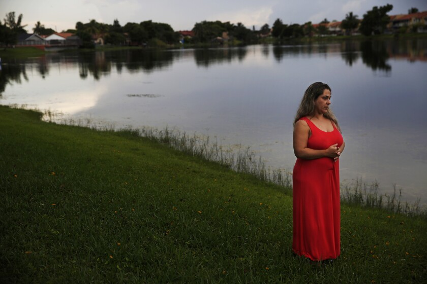 In this Aug. 6, 2019, photo, Barbara Rodriguez poses for a photo outside of her home in Hialeah, Fla. Her husband, Pablo Sanchez, is seeking asylum in the U.S., but was placed in detention and is now facing deportation to Cuba. (AP Photo/Brynn Anderson)