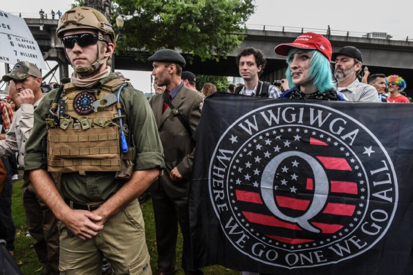 A person holds a banner referring to the Qanon conspiracy theory during a alt-right rally on August 17, 2019 in Portland, Oregon. Epoch Times has come to be known for spreading such conspiracy theories.