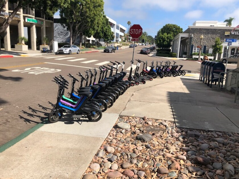 Electric bikes and scooters are stationed outside the Wall Street post office in La Jolla in violation of city staging rules.