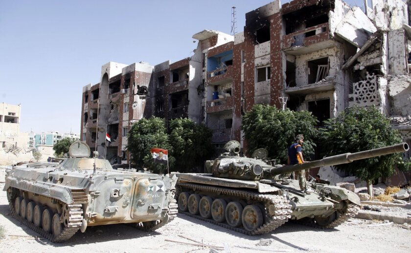 Government tanks sit idle in the recently recaptured town of Adra Al-Omaliya near Damascus, Syria. The U.N. has been urged to ban the trade of Syrian antiquities amid reports of looting in the region.