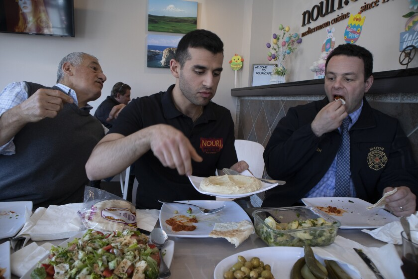 Andre Sayegh, the mayor of Paterson, N.J., right, eats with Albert and George Noury, who own the Nouri Cafe on Main Street in South Paterson. Sayegh is the first Arab American to lead the city.