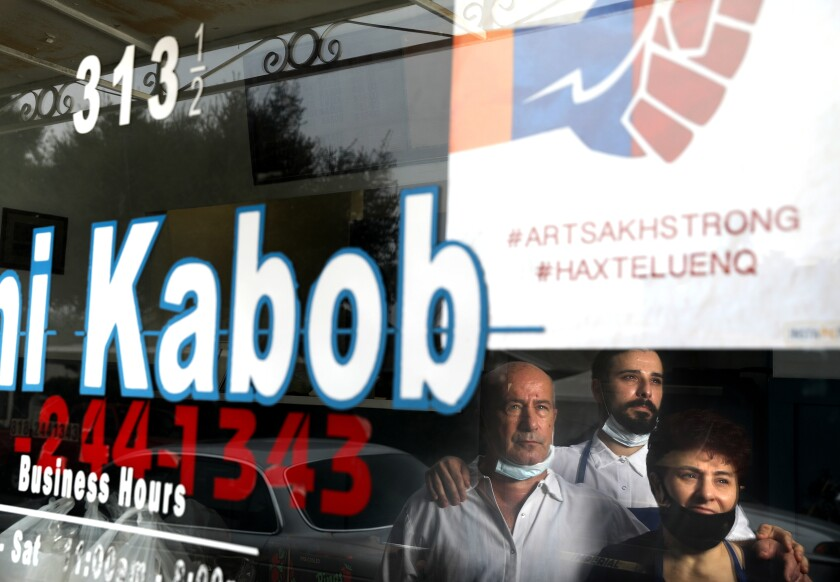 Three people reflected in window of restaurant with an Artsakh Strong sign