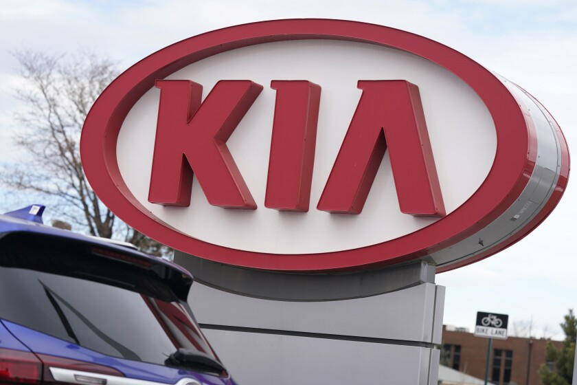 The company logo stands over a row of unsold 2021 Seltos models at a Kia dealership Sunday, Dec. 20, 2020, in Centennial, Colo. Kia is recalling more than 440,000 vehicles in the U.S. for a second time to fix a problem that can cause engine fires. The automaker, Tuesday, May, 18, 2021, also is telling owners to park them outdoors and away from structures because fires could happen when the engines aren't running. The recall covers certain Optima sedans from 2013 through 2015 and Sorento SUVs from 2014 and 2015. (AP Photo/David Zalubowski)
