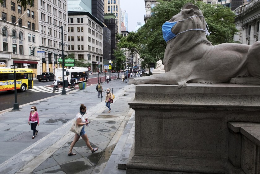 FILE - In this July 1, 2020, file photo, a face mask covers the mouth and nose of one of the iconic lion statues in front of the New York Public Library Main Branch in New York. New York City's public libraries will no longer charge late fees and will waive existing fines for overdue books and other materials, city officials announced Tuesday, Oct. 5, 2021. (AP Photo/Ted Shaffrey, File)