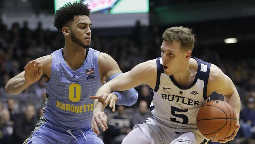 Butler's Paul Jorgensen (5) is defended by Marquette's Markus Howard (0) during the first half of an