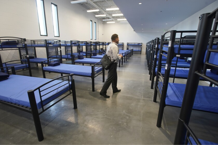 Preston Cochrane, executive director of Shelter the Homeless, walks through a room full of beds.