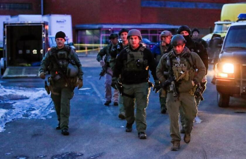 Heavily armed police officers walk from a parking lot after a shooting at the Henry Pratt Company in Aurora, Illinois, USA, Feb. 15, 2019. EPA/TANNEN MAURY