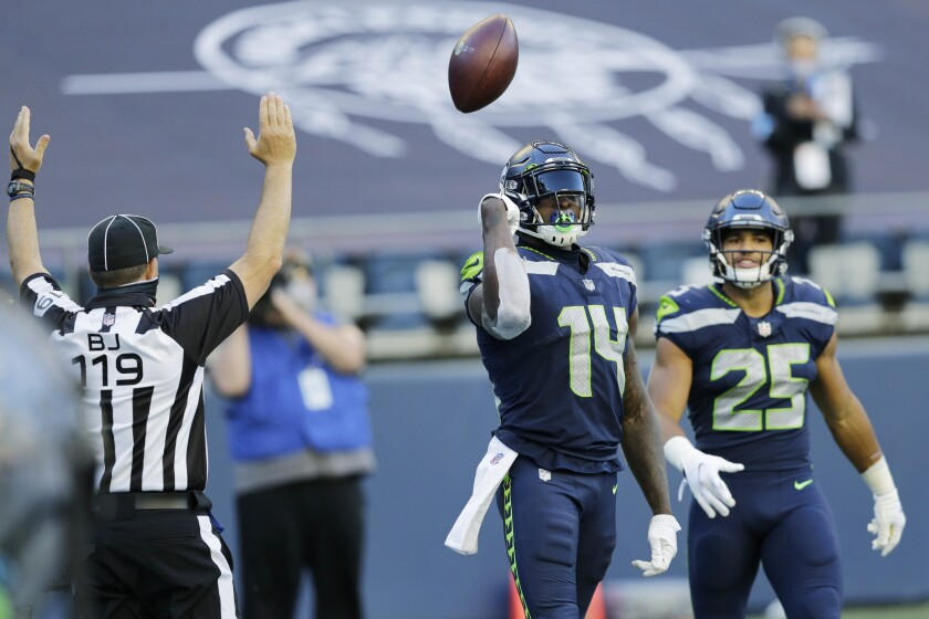 Seattle Seahawks wide receiver DK Metcalf (14) tosses the ball as he stands with running back Travis Homer (25) after Metcalf scored a touchdown against the Dallas Cowboys during the second half of an NFL football game, Sunday, Sept. 27, 2020, in Seattle. (AP Photo/John Froschauer)