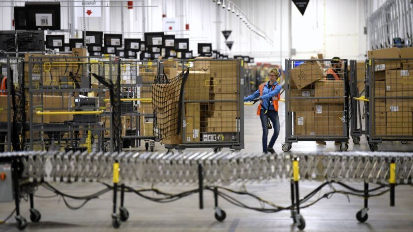 Workers move bins filled with boxes at the loading dock of an Amazon warehouse in Livonia, Mich.