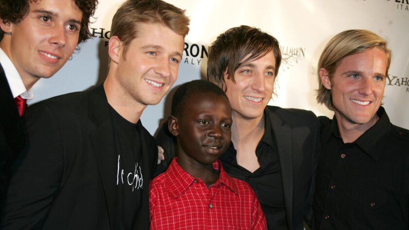 "Actor Benjamin McKenzie of ""The OC,"" second from left, is photographed with film makers Laren Poole, left, Bobby Bailey and Jason Russell, right, and Ugandan teen Emmy during the ""Red is for Emmy"" party for Invisible Children in Los Angeles, Tuesday, Nov. 15, 2006."