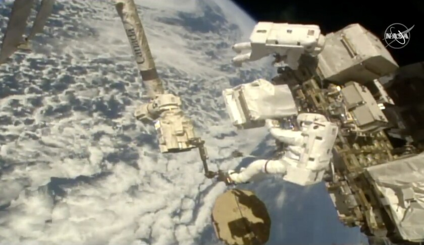 In this image taken from NASA video Italian astronaut Luca Parmitano, lower right, holds a bundle of new pumps for the Alpha Magnetic Spectrometer as he and U.S. astronaut Andrew Morgan work to revitalize a cosmic ray detector outside the International Space Station on Monday, Dec. 2, 2019. Monday's spacewalk is the third in nearly three weeks for the pair and is the culmination of years of work to repair the Alpha Magnetic Spectrometer. (NASA via AP)