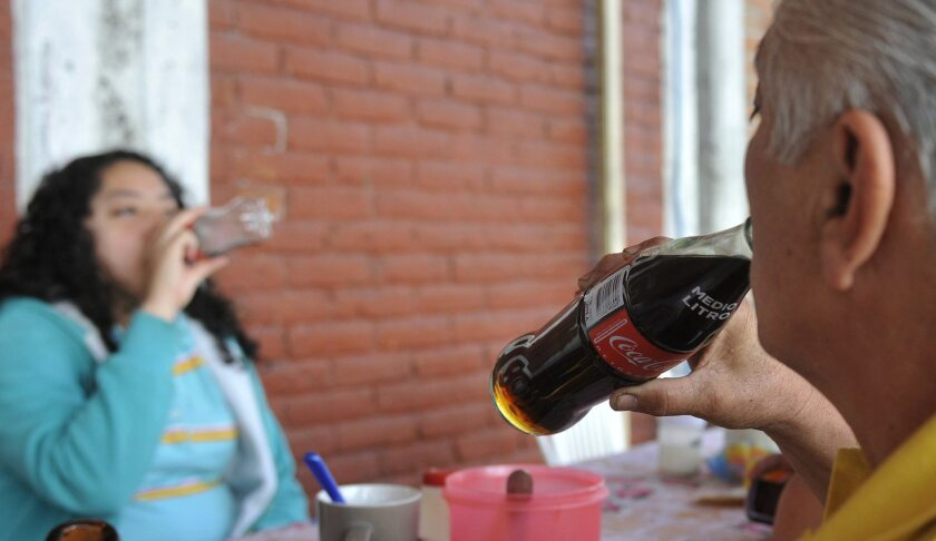 People drink soft drinks in Mexico City. Mexico has one of the world's highest rates of obesity, recently surpassing the United States, and higher taxes on chips, sugary drinks and other or junk food are being applauded by health experts. But many in the business community are less than happy.