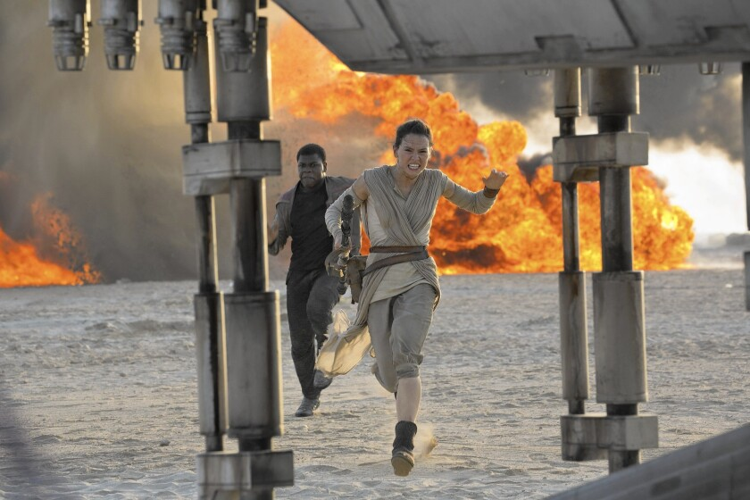 """Daisy Ridley, right, as Rey, and John Boyega as Finn, in a scene from the film, """"Star Wars: The Force Awakens."""""""