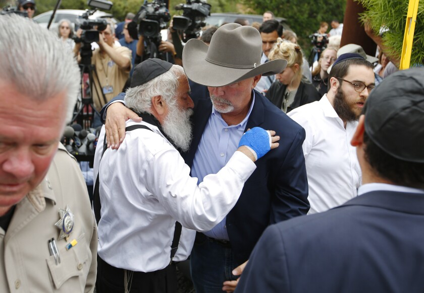 Rabbi Yisroel Goldstein of Chabad of Poway hugs Poway Mayor Steve Vaus the day after a deadly shooting took place at the synagogue on April 28. Goldstein was shot and lost a finger on his right hand.