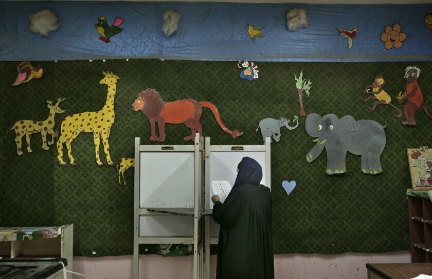 FILE --In this Sunday, Nov. 22, 2015 file photo, a woman reads a ballot, inside a polling station for women only during the second phase of the parliamentary elections, in Qalyoubiya governorate, north of Cairo Egypt. Egyptians in nearly half the country, including the capital Cairo, are voting in the second stage of parliamentary elections that will produce the country's first legislature since a chamber dominated by Islamists was dissolved by a court ruling in 2012. (AP Photo/Nariman El-Mofty, File)