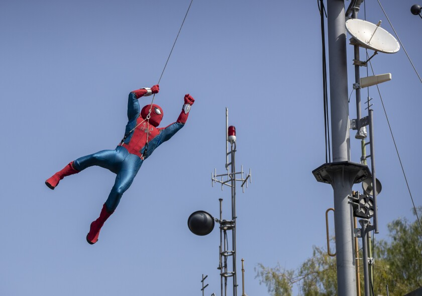 A robot Spider-Man soars through the air while performing