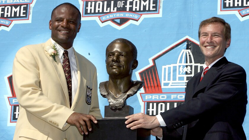 Warren Moon, left, poses with his bust and his presenter Leigh Steinberg after Moon's induction cere