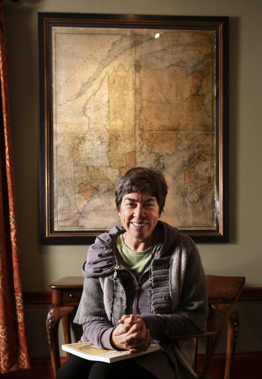 In this March 14, 2011 file photo, Roxanne Quimby, the founder of Burt's Bees, poses in front of a 180-year-old map of Maine at her home in Portland, Maine.