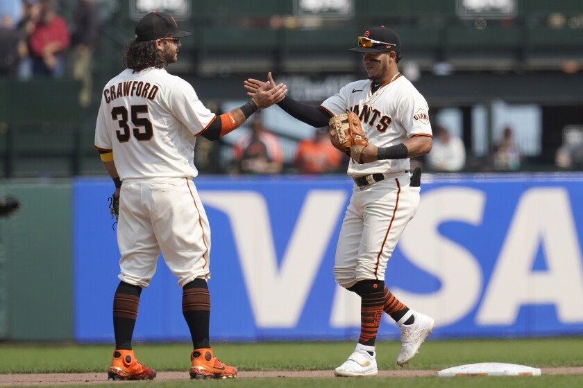 San Francisco Giants' Brandon Crawford, left, celebrates with Thairo Estrada after the Giants defeated the Milwaukee Brewers 5-1 in a baseball game in San Francisco, Thursday, Sept. 2, 2021. (AP Photo/Jeff Chiu)