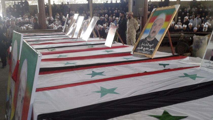 In this photo released by the Syrian official news agency SANA, mourners attend a mass funeral of pe