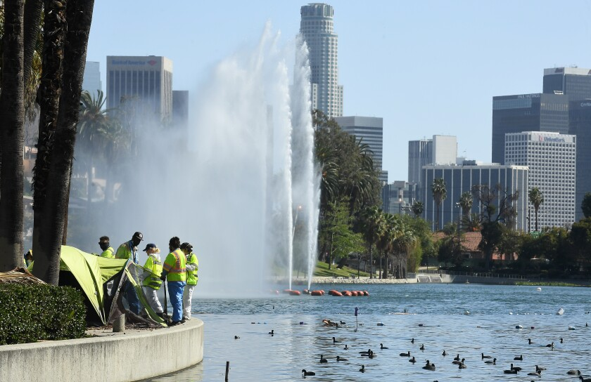 Work crews look over a tent next to Echo Park Lake, with the L.A. skyline in the background.