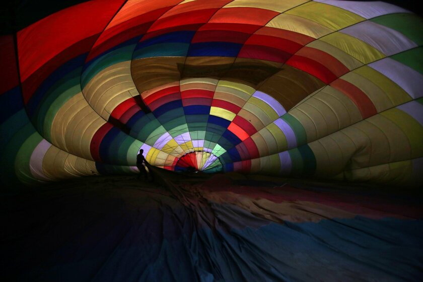 A balloonist prepares to inflate his hot air balloon before the launch during Lucknow balloon festival, in Lucknow, India, Monday, Feb. 15, 2016. The three-day festival is to boost the tourism and generate more employment opportunities in the state of Uttar Pradesh. (AP Photo/Rajesh Kumar Singh)