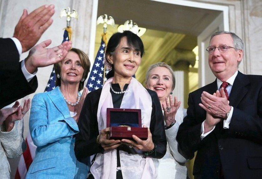 Myanmar opposition politician Aung San Suu Kyi holds her Congressional Gold Medal as House Minority Leader Nancy Pelosi (D-San Francisco), left, U.S. Secretary of State Hillary Rodham Clinton and Senate Minority Leader Mitch McConnell (R-Ky.) applaud at the U.S. Capitol.