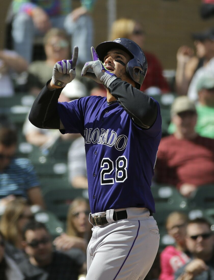 Colorado Rockies' Nolan Arenado, center, gestures skyward as he scores after hitting his second home run of the game during the fifth inning of a spring training baseball game against the Arizona Diamondbacks Tuesday, March 29, 2016, in Scottsdale, Ariz. (AP Photo/Jae C. Hong)