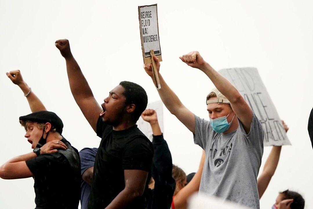People chant outside a Minneapolis police station as they protest the death in custody of George Floyd.