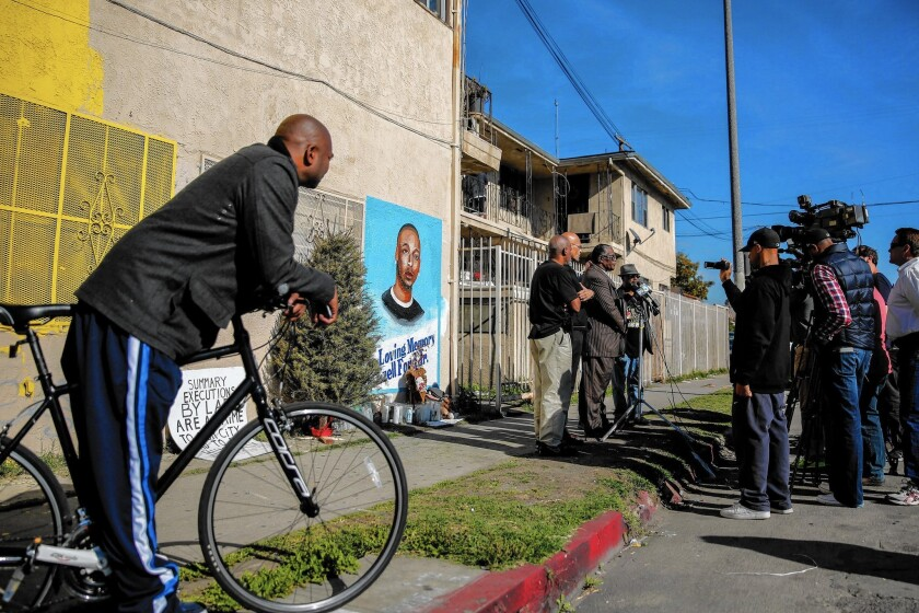 Edsell Ford, left, the father of Ezell Ford, listens to a news conference with Los Angeles civil rights leaders at the corner of 65th Street and Broadway in South Los Angeles, where his son was killed.