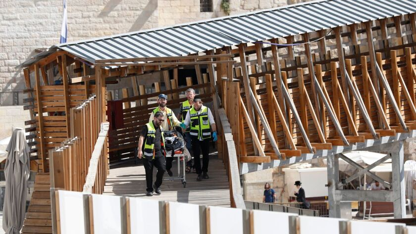 A body is removed from the Temple Mount compound in Jerusalem's Old City after a gun battle at the holy site on July 14.