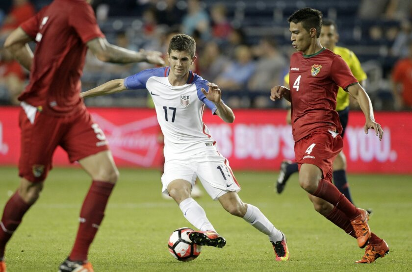 U.S. forward Christian Pulisic (17) attempts to drive past Bolivia defender Diego Bejarano (4) during the second half of an international friendly soccer match, Saturday, May. 28, 2016, in Kansas City, Kan. The United States won 4-0. (AP Photo/Colin E. Braley)
