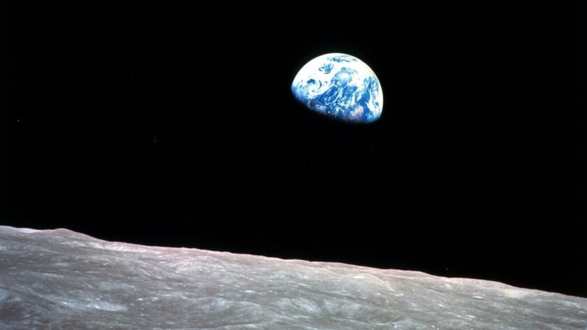 This Dec. 24, 1968, photo taken during the Apollo 8 mission shows Earth beyond the surface of the moon.