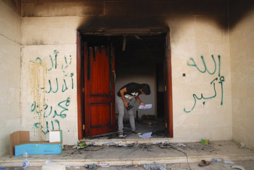 A man looks at documents at the U.S. consulate in Benghazi, Libya, after an attack that killed four Americans.