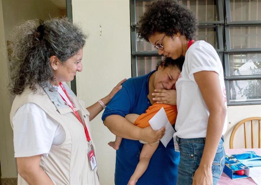 Fotografía cedida por la ONG Mercy Corps donde aparece sus miembros Karla Peña (i) y Pardis Barjesteh (d), mientras consuelan a Stephanie Colon Medina (c) quien abraza llorando a su hijo Anthony Jaffeth, de 1 año de edad, tras recibir ayuda el pasado 17 de noviembre de 2018, en el municipio de Maricao, la segunda población más pequeña de Puerto Rico. EFE/A. Valentín/Mercy Corps/SOLO USO EDITORIAL/NO VENTAS