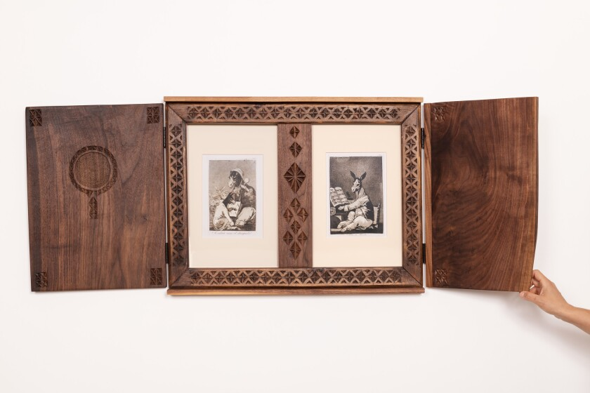 A triptych-style frame in dark, hand-tooled walnut features two prints by Goya showing donkeys