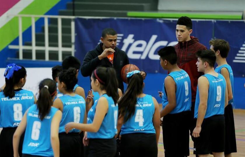 El entrenador de los Suns de Phoenix, Earl Watson (i), y el jugador Devin Booker (d) imparten una clase de baloncesto a jóvenes mexicanos en Ciudad de México.
