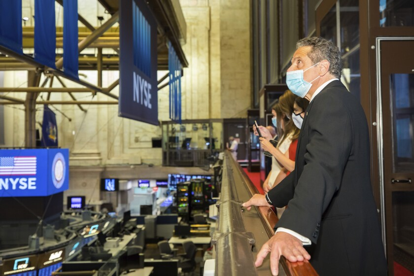 New York Gov. Andrew Cuomo looks over the trading floor at the New York Stock Exchange, which reopened with social distancing guidelines on Tuesday.