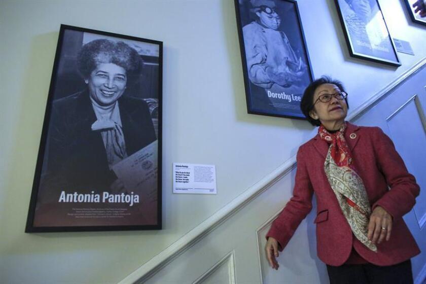 """La concejala de Nueva York, Margaret Chin, baja las escaleras junto a un retrato de la educadora puertorriqueña Antonia Pantoja (1922-2002) durante la inauguración de la exposición """"Voces de Mujeres: Construyendo la Ciudad"""" este viernes en la sede de la alcaldía en Nueva York (EEUU). EFE"""