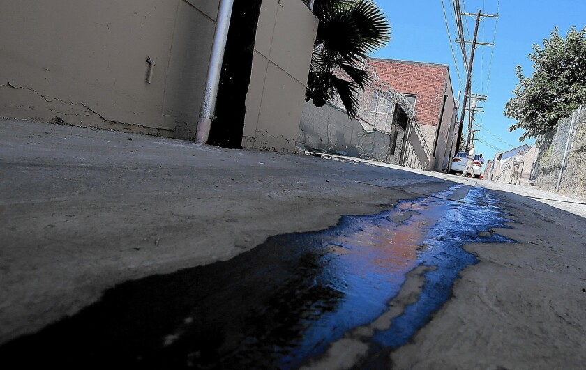 Rick Silva, a Department of Water and Power employee, tries to trace the source of water running down an alley in L.A.'s Temple-Beaudry neighborhood. Californians have substantially reduced their water usage.
