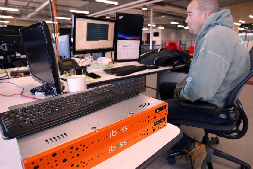 Chris Sweigart, senior software engineer for iboss Cybersecurity, works at his movable desk near two orange-coloredserver filters.