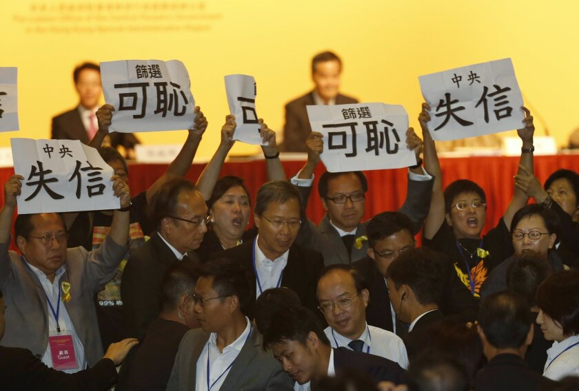 Pro-democracy lawmakers display placards against Li Fei, deputy secretary general of the National People's Congress' Standing Committee, during a briefing session in Hong Kong Monday, Sept. 1, 2014. Hong Kong pro-democracy legislators have disrupted the Beijing official's speech as he sought to exp