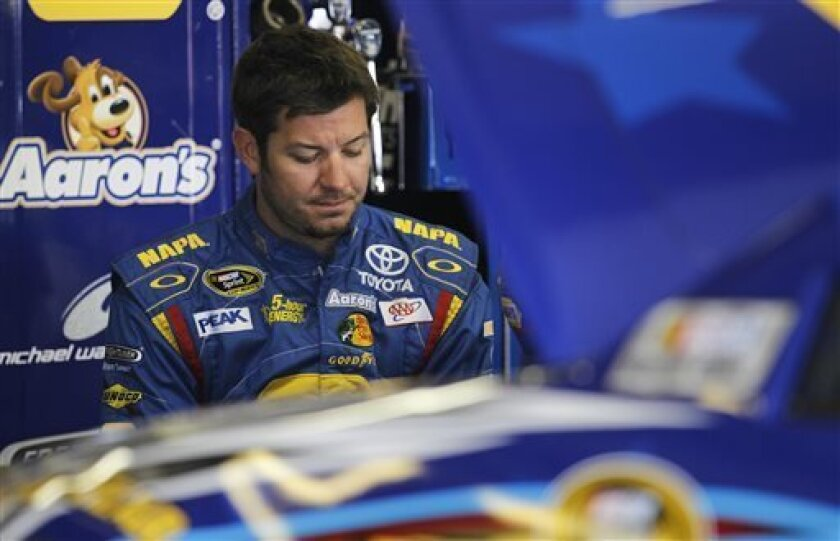 FILE - In this July 12, 2013 file photo, NASCAR driver Martin Truex Jr. reflects during practice at New Hampshire Motor Speedway in Loudon, N.H. NASCAR's investigation into Clint Bowyer's spin at Richmond ultimately uncovered a series of deliberate actions by Michael Waltrip Racing to alter the race results and the field for the Chase for the Sprint Cup championship. The sordid saga concluded Monday, Sept. 10, 2013, with a hefty penalty that saw Ryan Newman replace Martin Truex Jr. in the Chase