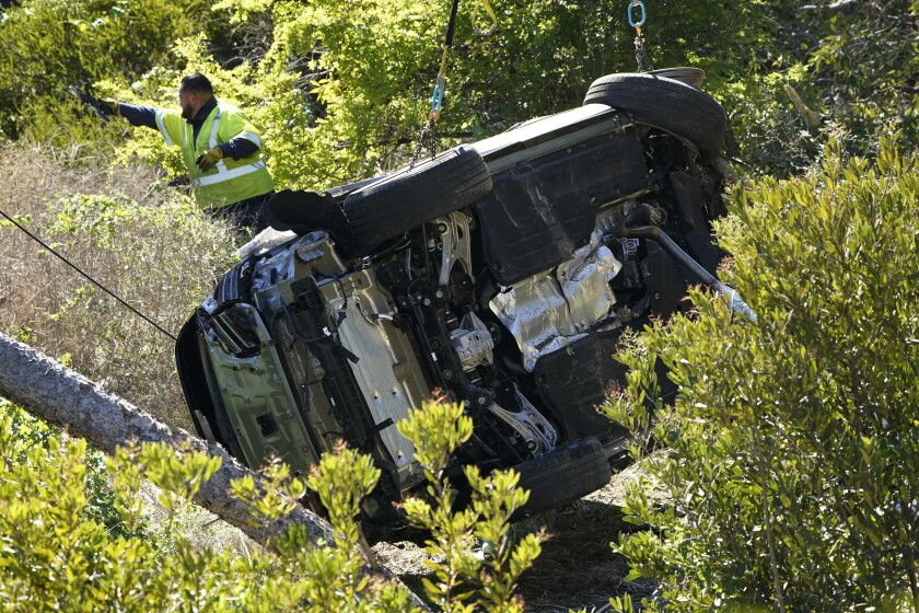 Workers move a vehicle on its side after a rollover accident involving golfer Tiger Woods Tuesday, Feb. 23, 2021, in Rancho Palos Verdes, Calif., a suburb of Los Angeles.. Woods suffered leg injuries in the one-car accident and was undergoing surgery, authorities and his manager said. (AP Photo/Marcio Jose Sanchez)
