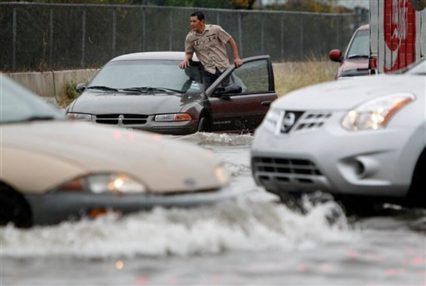 A stranded motorist surveys the situation at the intersection of Fondren and Harwin Drive as a storm continues to move through the area on Monday, Jan. 9, 2012, in Houston. City roads were flooded and thousands of Houston residents, including at least five schools, were without electricity Monday after powerful thunderstorms ploughed through the area prompting a tornado warning and dumping several inches of rain and hail on the drought-stricken region. (AP Photo/Houston Chronicle, Mayra Beltran)