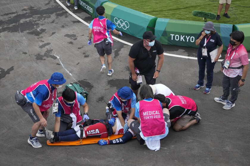Medics prepare to carry away on a stretcher Connor Fields of the United States after he crashed at the first bend in the men's BMX Racing semifinals at the 2020 Summer Olympics, Friday, July 30, 2021, in Tokyo, Japan. (AP Photo/Ben Curtis)