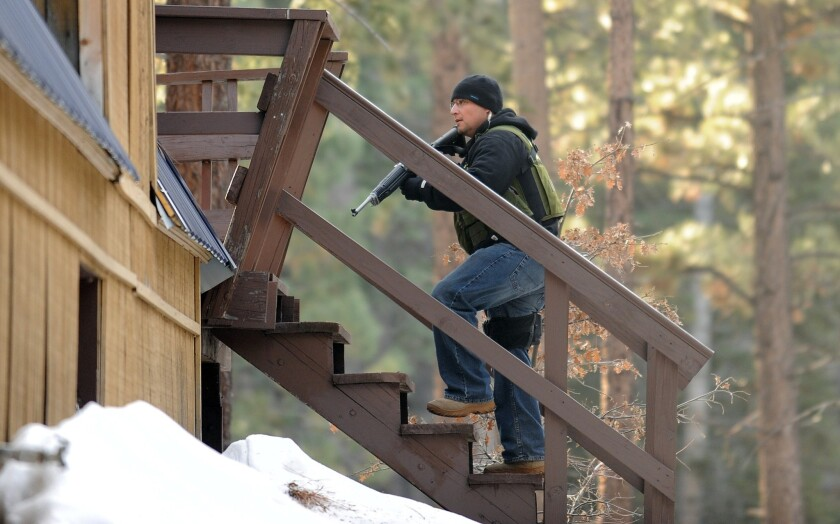A San Bernardino County officer checks a house on Sylvan Glen Avenue in Big Bear Lake for shooting suspect Christopher Jordan Dorner. The ex-police officer's truck was found burning in the mountain area.