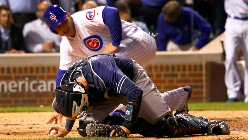 San Diego Padres catcher Austin Hedges stays on the ground after tagging out Chicago Cubs' Anthony R