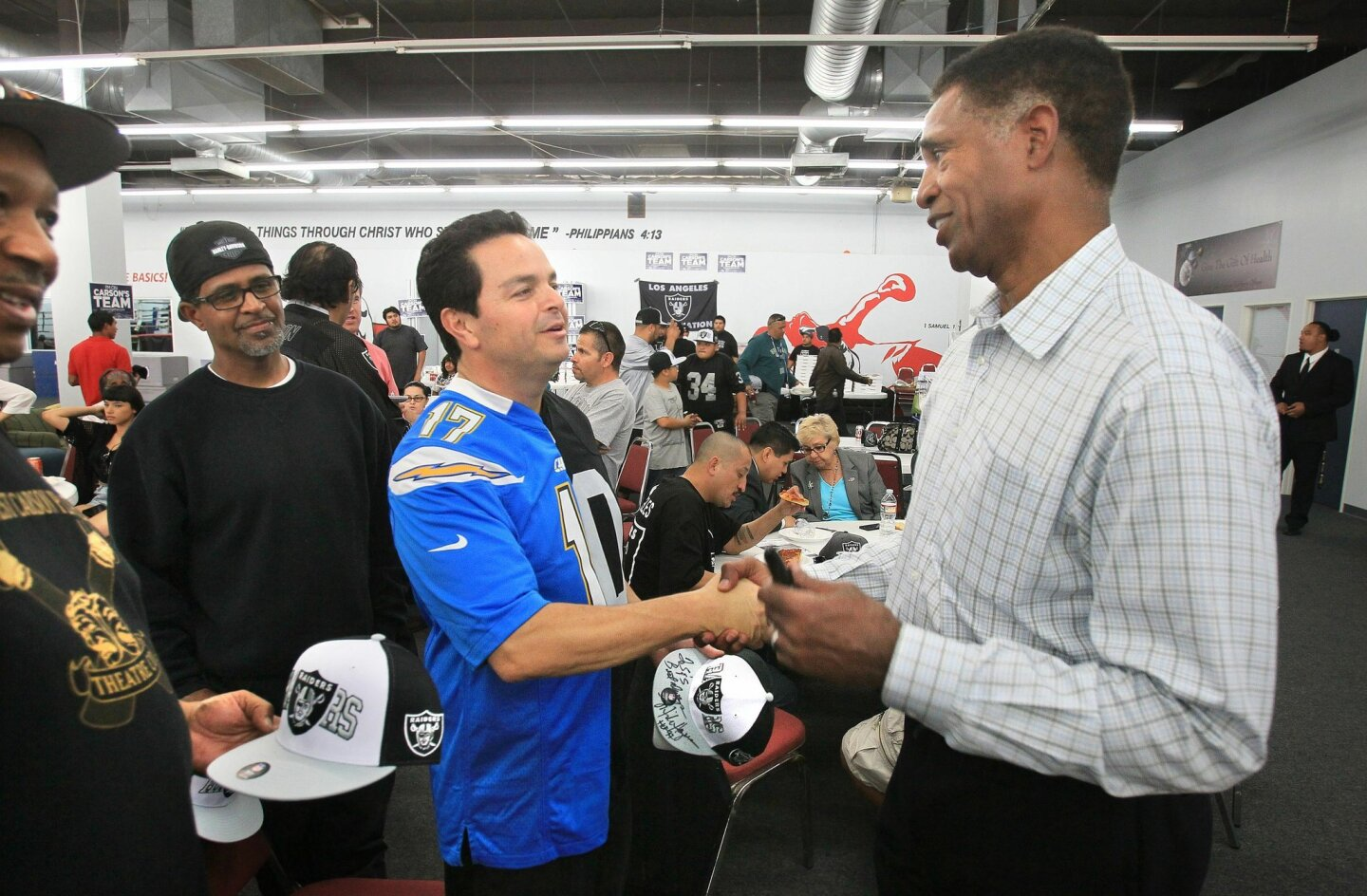 Mike Haynes, at right, a former Raiders player in the NFL Hall of Fame, and San Diego resident, shakes hands with Carson Councilmember Albert Robles wearing a special Chargers/Raiders jersey after he autographed a Raiders hat for him.
