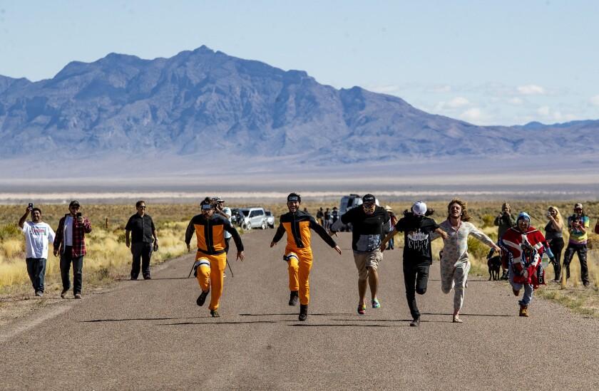 Alien enthusiasts Naruto run toward the back gate of Area 51